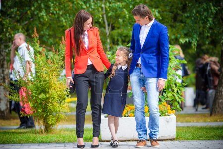 Photo for Mother and father brings little daughter to school. - Royalty Free Image