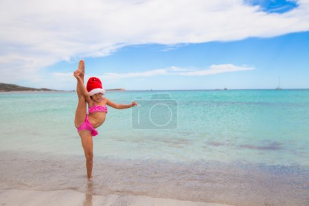 Photo for Smiling girl making stretching exercise in Santa Hat on white beach - Royalty Free Image