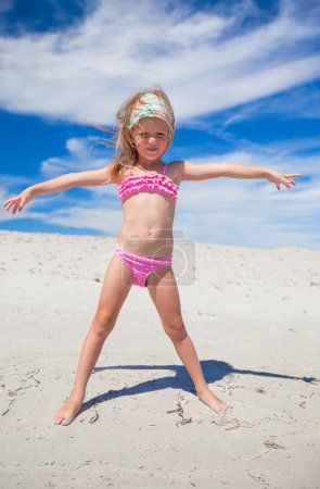 Adorable little girl in beautiful swimsuit have fun at tropical beach