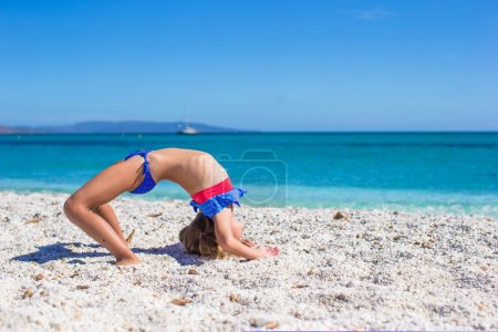 Cute little sporty girl on white tropical beach and having fun