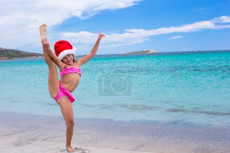 Smiling girl making stretching exercise in Santa Hat on white beach