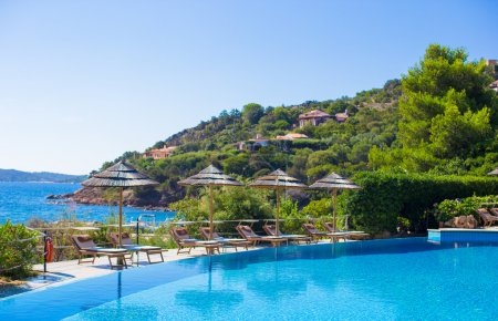 Wooden deck chairs near infinity pool in luxury resort