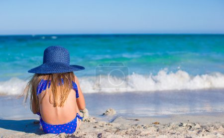 Rear view of adorable little girl in big blue straw hat at white beach