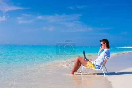 Photo for Young man using laptop on the beach - Royalty Free Image