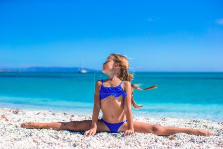 Photo for Cute little girl having fun making leg-split and enjoying vacation on tropical beach - Royalty Free Image