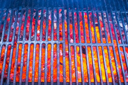Empty black cast iron grill with hot red glowing coals
