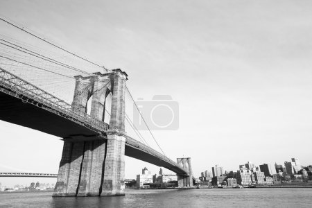 Brooklyn Bridge over East River viewed from New York City. Black and white.