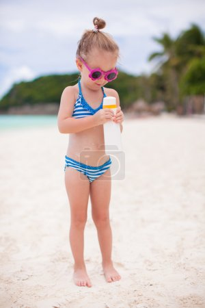 Photo for Little adorable girl in swimsuit holds suntan lotion bottle - Royalty Free Image