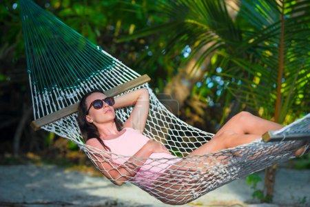 Woman in swimsuit relaxing on hammock sunbathing on vacation