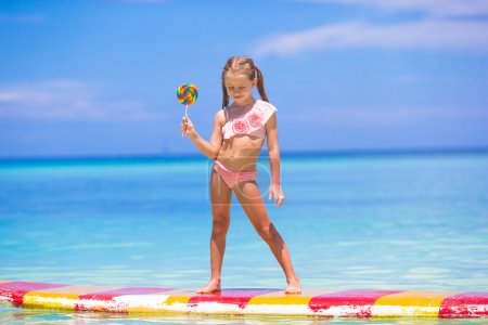 Little girl with lollipop have fun on surfboard in the sea