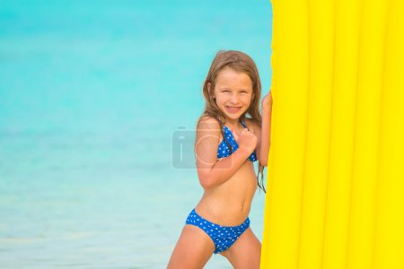 Little girl with air mattress on summer vacation at tropical beach