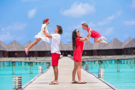 Happy family of four on wooden jetty during summer vacation at luxury resort