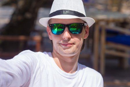 Young man making his selfie on beach at outdorr cafe