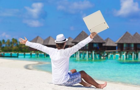 Photo for Young man working on laptop at tropical beach - Royalty Free Image