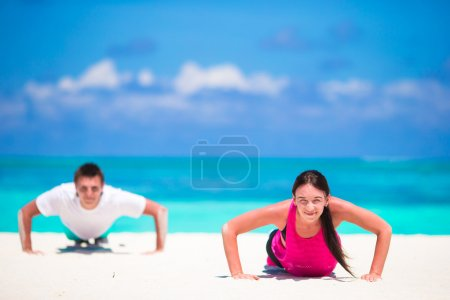 Young fitness couple doing push-ups during outdoor cross training workout on tropical beach