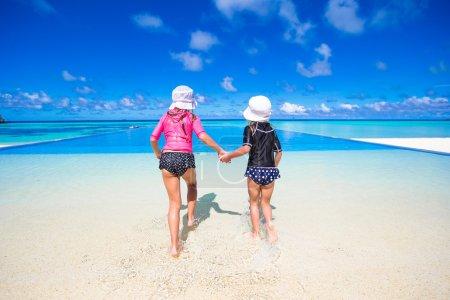 Photo pour Mignonnes tout-petits filles debout en eau peu profonde à la plage exotique - image libre de droit