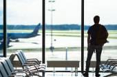 Silueta muže čekají na palubu letu na letišti