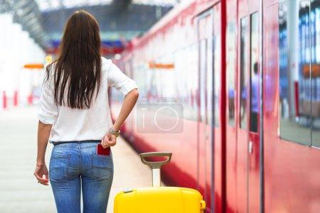 Jeune fille blanche avec des bagages à la gare, vous voyagez en train