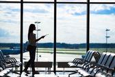 Silueta ženy v letištní hale čeká na letu letadel