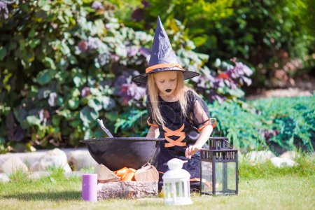 Adorable little girl wearing witch costume casting a spell on Halloween. Trick or treat.