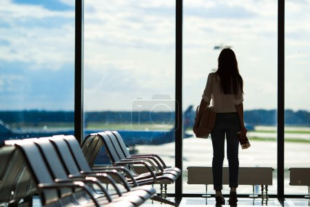 Young woman near window in an airport lounge waiting for flight aircraft