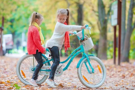 Adorable little girls riding a bike at beautiful autumn day outdoors