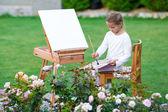 """Постер, картина, фотообои """"Очаровательны маленькая девочка нарисовать картину на мольберт на теплый день на открытом воздухе"""""""