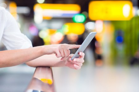 Closeup cell phone at airport in female hands