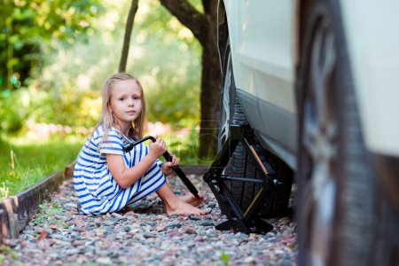 Photo for Little girl helping father to change a car wheel outdoors on beautiful summer day - Royalty Free Image