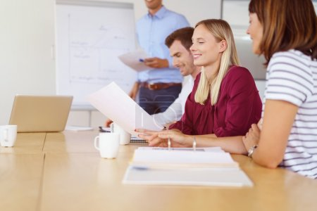 Smiling woman with coworkers at desk