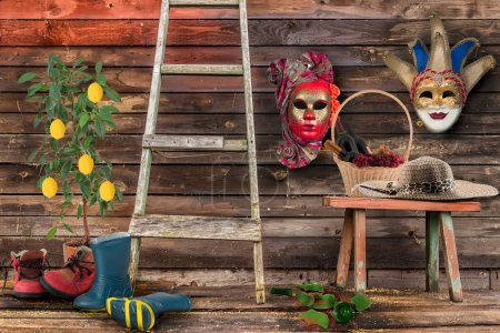 Photo pour Deux masques de carnaval accroché mur bas en bois banc en osier panier bouteilles vin étage de chapeau de paille de raisins cassé le pot de céramique arbre, femmes bouteille escalier deux paires chaussures hommes de citron - image libre de droit
