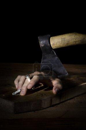 Photo pour Main de l'homme avec une cigarette, coupée avec une hache. - image libre de droit
