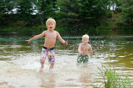 Two Young Children Swimming and Playing in Lake