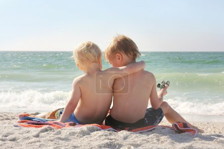Young Brothers Sitting on Beach By Ocean with Arms Around Each O