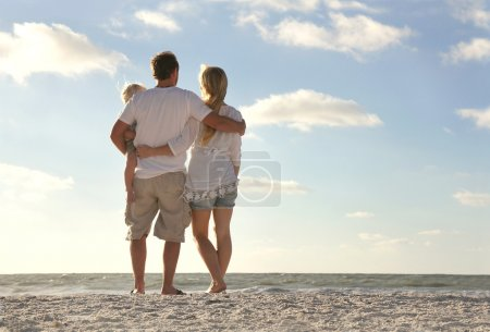 Happy Family On Beach Vacation Looking at Ocean