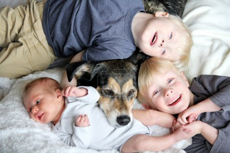 Three Happy Young Children Snuggling with Pet Dog in Bed