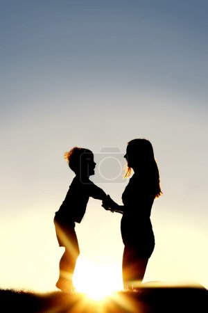 Silhouette of Mother and Young Child Holding Hands at Sunset