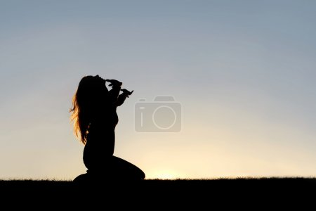 Photo for A silhouette of a woman kneeling down with her hands in the air, praying, thanking, and surrendering to God. - Royalty Free Image