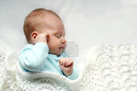 Bebé recién nacido dormido en mantas blancas