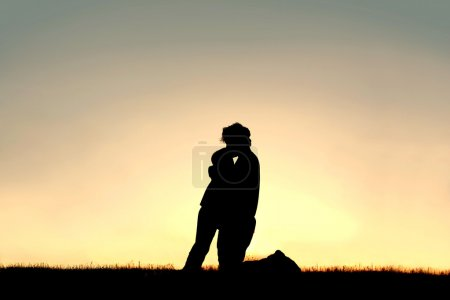 Silhouette of Father Lovingly Kissing Child on Forehead at Sunse