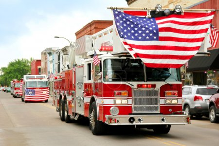 Photo for A group of fire trucks with American flags on them drive down the road in a small town American Parade during a festival event. - Royalty Free Image