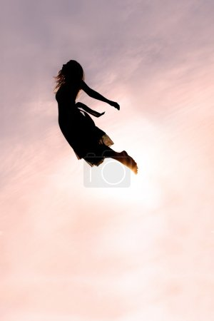 Silhouette of Woman Flying through Sky