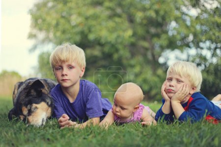 Three Bored Young Children and Dog Relaxing Outside