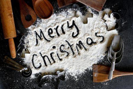 Photo for The words Merry Christmas are written in baking flour surrounded by a border of vintage cooking supplies and cookie cutters. - Royalty Free Image