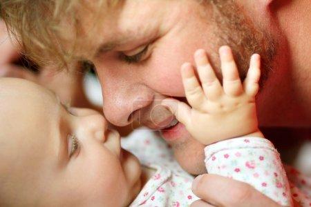 Photo pour Un père heureux joue avec sa fille nouveau-née, touchant affectueusement le nez pendant qu'elle pose sa main sur sa joue. Profondeur de champ faible . - image libre de droit