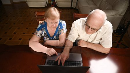 An elderly couple is sitting at a computer and looking for information on the Internet. View from above.