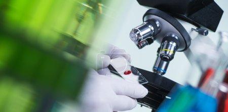 Photo pour Scientifique de laboratoire tenant une lame contenant un échantillon de sang avec un microscope en arrière-plan - image libre de droit