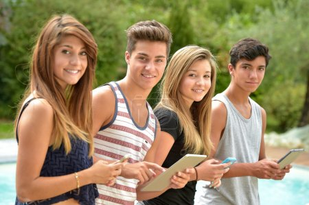 Young teenagers playing on tablet and phone