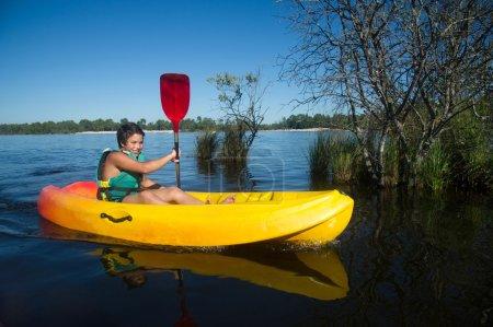 Teen making canoe kayak on a lake