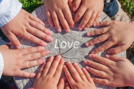 Photo pour Les mains de quelques enfants sur un vieux tronc avec le mot Amour au centre d'eux - image libre de droit